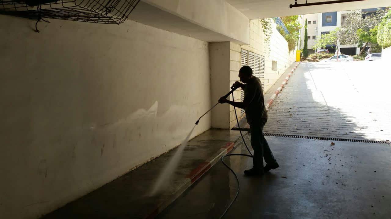 עובד מנקה מדרכה בחניון עם צינור מים